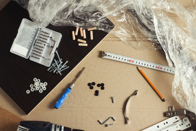 Strumenti per il montaggio di mobili, dettagli di mobili, film di avvolgimento, viti su un foglio di cartone. costruire mobili manualmente. concept workshop. vista piana, vista dall'alto