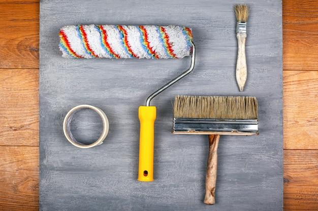 Strumenti per la pittura di pareti e soffitti. nappe di rullo e nastro adesivo su sfondo grigio vista dall'alto.