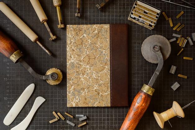 Strumenti per la rilegatura. natura morta di vari strumenti di commercio per l'artigianato di rilegatura a mano e sfondo di goffratura