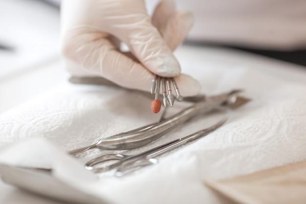 Strumenti per manicure, maestro di manicure che disinfetta il suo apparato.