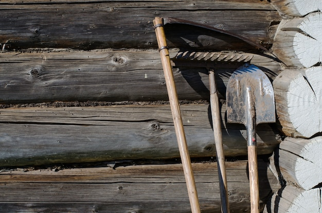 Strumento da giardino: falce, pala, rastrello. parete della casa rurale fatta da tronchi di legno