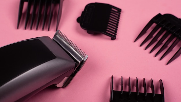 Strumento da parrucchiere. close-up tosatrice su uno sfondo rosa con ugelli di diverse dimensioni.