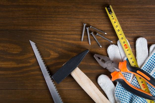 Strumento di costruzione su un tavolo di legno. chiodi, martello, seghetto