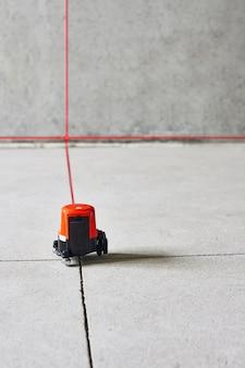 Strumento di misurazione del livello laser in cantiere sul pavimento nella stanza vuota di cemento