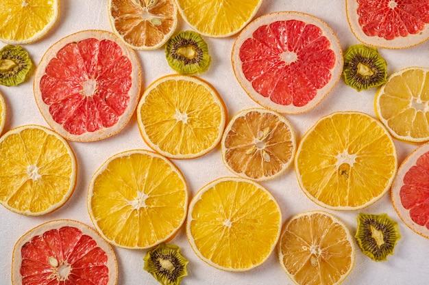 Struttura creativa della frutta dell'alimento con il pompelmo, l'arancia, il kiwi ed il limone secchi sulla vista bianca e superiore