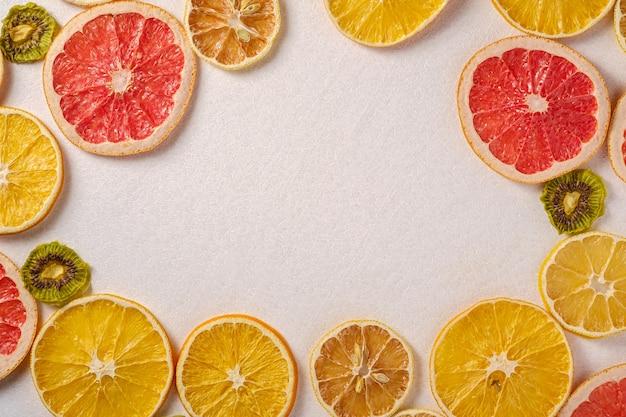 Struttura creativa della frutta dell'alimento con il pompelmo secco, il kiwi, l'arancia ed il limone, vista superiore, spazio bianco vuoto della copia del fondo