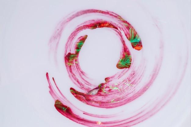 Struttura creativa della vernice rossa e verde nel modello del mulinello