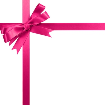 Struttura d'angolo verticale del confine dell'arco rosa del nastro del regalo isolata su bianco.
