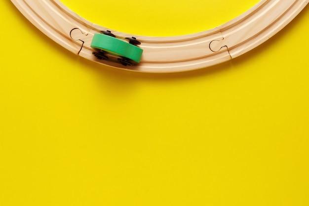 Struttura dei giocattoli dei bambini su backround giallo, ferrovia di legno del giocattolo e treno. vista dall'alto. flatlay. copia spazio per il testo