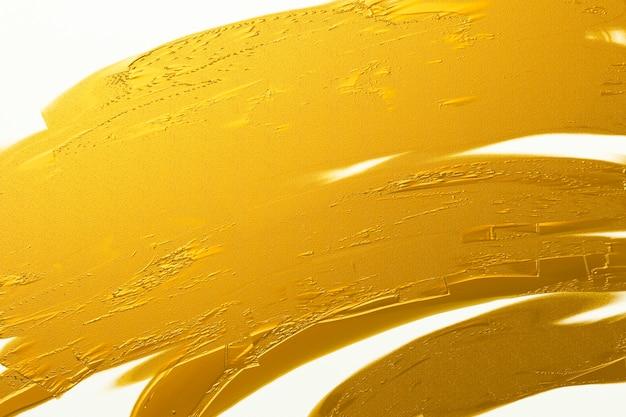 Struttura del colpo della spazzola dell'oro sul fondo bianco della tela