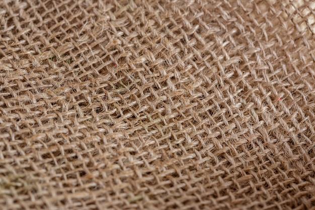 Struttura del fondo marrone beige del primo piano del tessuto della tela