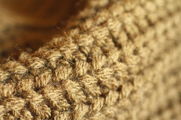 Struttura del maglione della lana naturale tricottata colore ocra del primo piano estremo