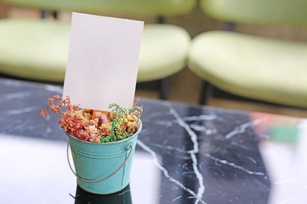Struttura del menu dell'etichetta della carta in bianco bianca in mini vaso di fiori sulla tavola al ristorante della barra.