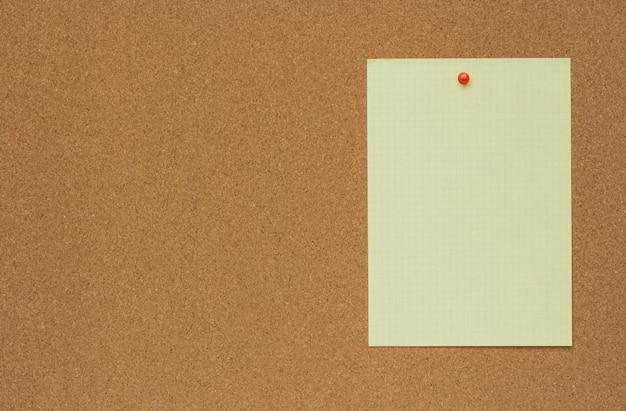 Struttura del primo piano di uno strato del bordo del sughero marrone con un foglio di carta