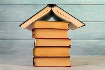 Struttura della casa fatta con libri d'epoca contro la parete in legno