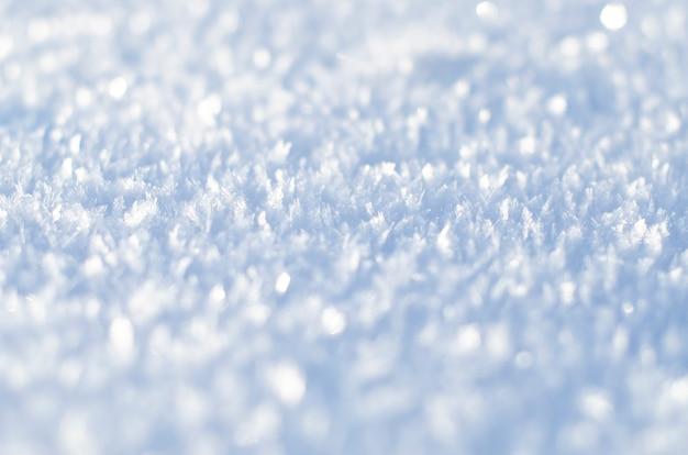 Struttura della neve con il primo piano dei fiocchi di neve. sfondo di neve per cartolina di natale o carta da parati.