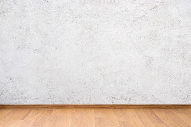 Struttura della parete del cemento bianco e pavimento di legno marrone