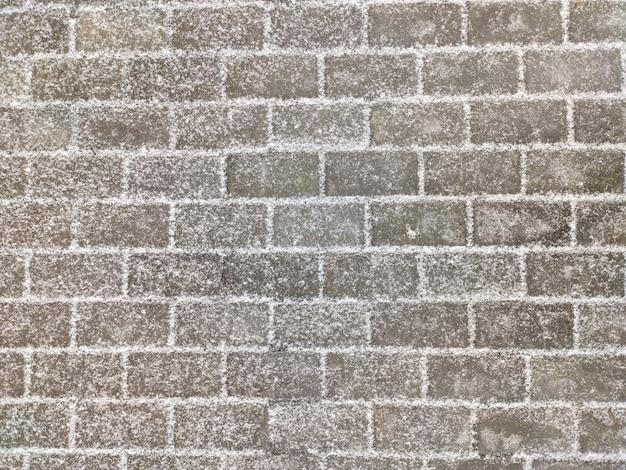 Struttura della pavimentazione delle mattonelle di pietra rettangolari grige coperte di neve leggera