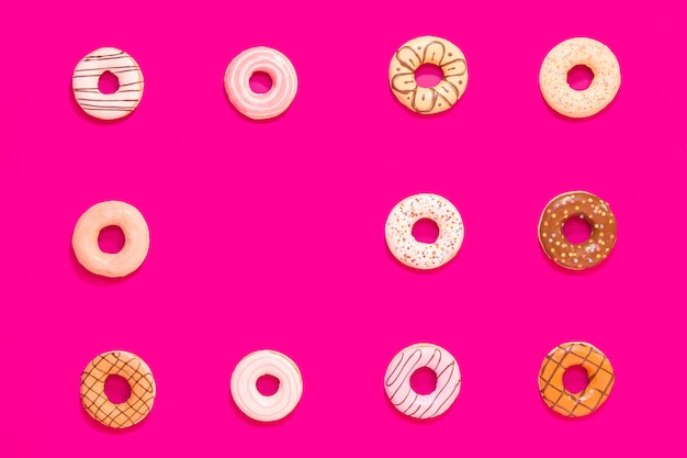 Struttura delle ciambelle multicolori su fondo rosa. dolci e cibo