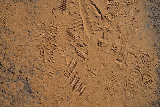 Struttura delle stampe del piede di scarpe su sfondo sabbia dorata