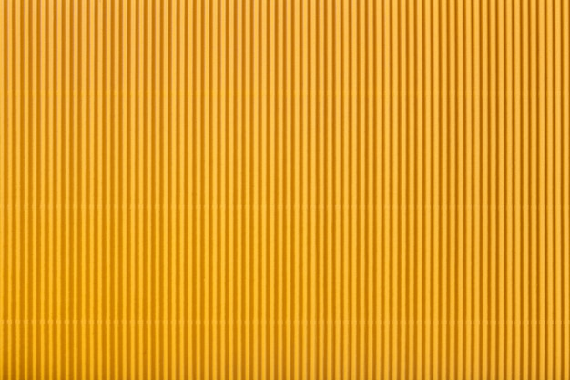 Struttura di carta gialla ondulata, macro. motivo a strisce