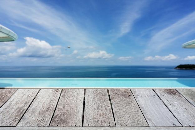 Struttura di legno del terrazzo del pavimento con il mare tropicale del fondo di estate della sfuocatura della piscina nella stagione estiva