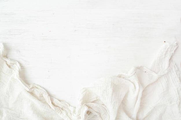 Struttura di legno, fondo di legno bianco con il tovagliolo della cucina, verticale