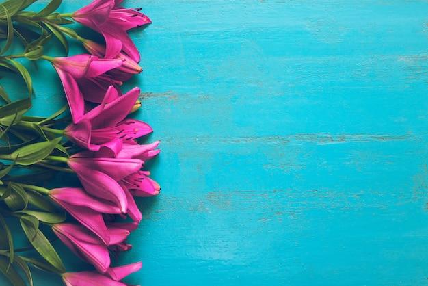 Struttura di menzogne dei gigli di giardino freschi sulla vecchia tavola di legno dipinta. bellissimo floreale