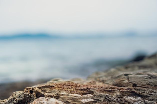 Struttura di pietra nera per spettacolo prodotto con sfondo spiaggia.