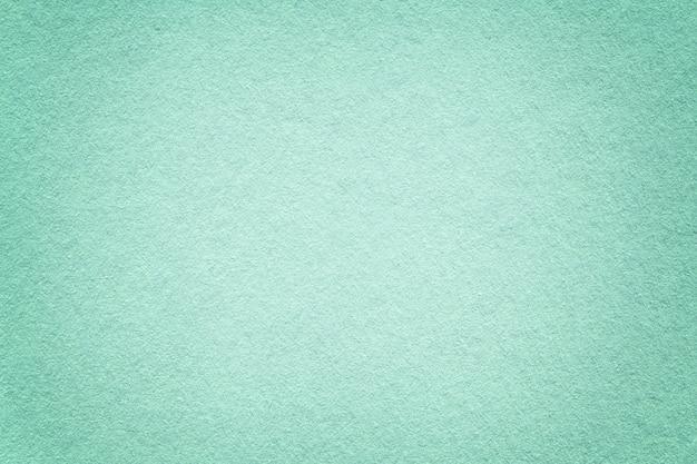 Struttura di vecchio fondo leggero della carta del turchese, primo piano. struttura di denso cartone smeraldo.