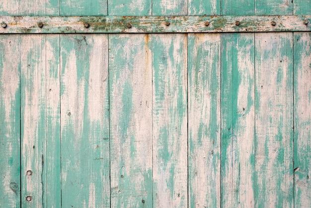 Struttura di vecchio fondo rustico di legno con la pelatura della pittura blu-chiaro con gli elementi arrugginiti del metallo.