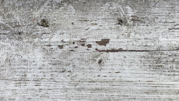 Struttura di vecchio legno con la pelatura della pittura bianca