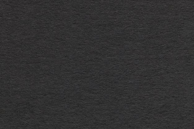 Struttura di vecchio primo piano di carta grigio. struttura di un cartone denso. lo sfondo nero.
