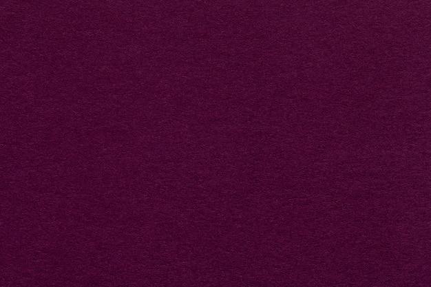 Struttura di vecchio primo piano di carta porpora scuro. lo sfondo magenta