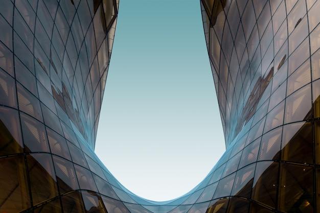 Struttura di vetro a forma di u con il cielo blu