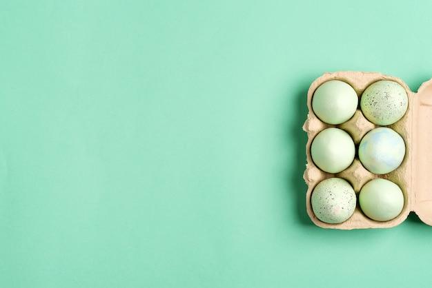 Struttura festiva di pasqua dalla scatola di carta delle uova dipinte verde fatto a mano su colore verde.