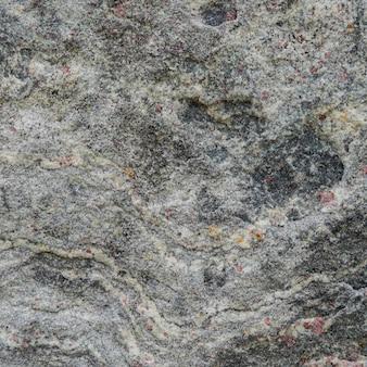 Struttura grigia di una pietra con macchie rosa.