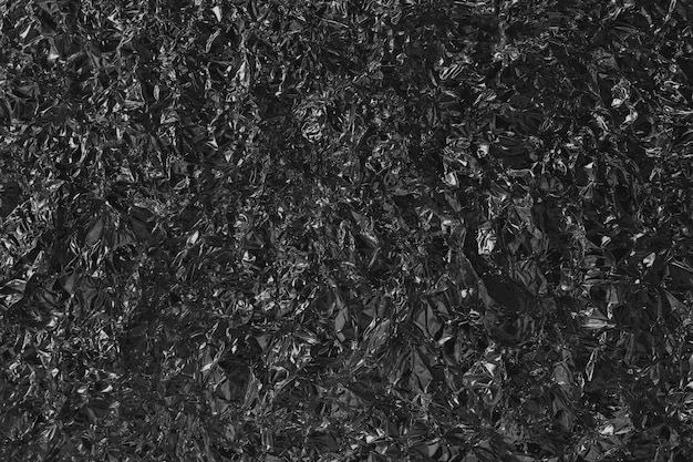 Struttura lucida nera nera della stagnola del metallo, carta da imballaggio astratta con alta risoluzione per fondo