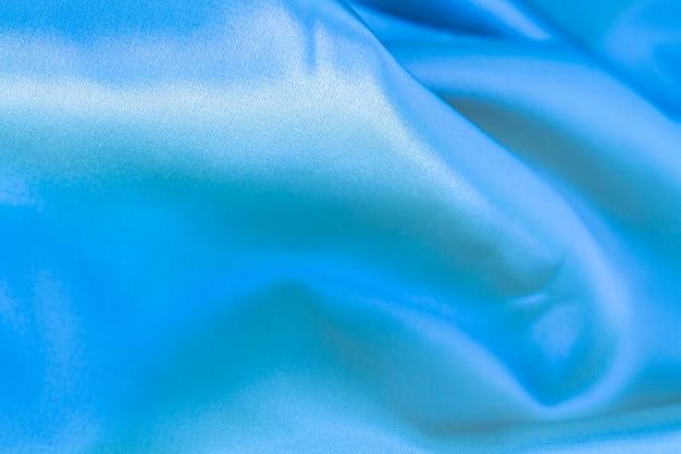 Struttura materiale del tessuto blu con lo spazio della copia