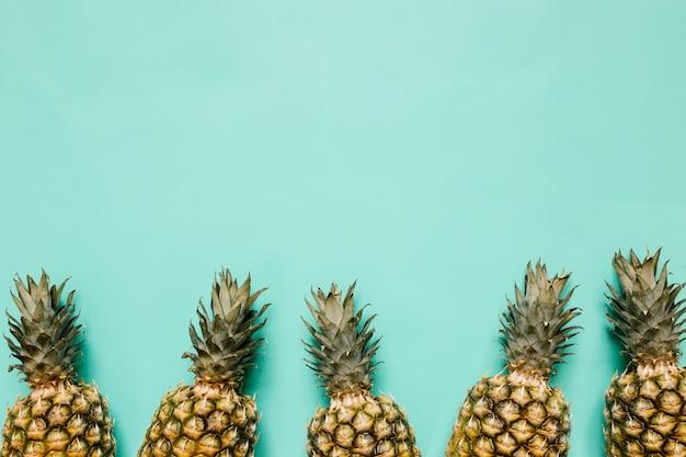 Struttura matura del confine degli ananas sul fondo del turchese isolato. concetto tropicale alla moda di stile minimalista. spazio vuoto per testo, copia, lettere.