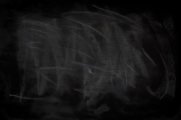 Struttura nera del grunge con copyspace. gesso astratto sfregato sulla lavagna.