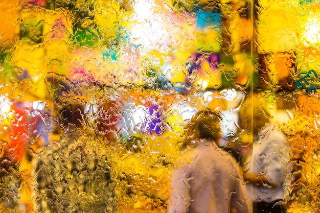 Struttura variopinta del fondo di concetto della sfuocatura delle gocce di acqua sulla finestra di vetro con la gente