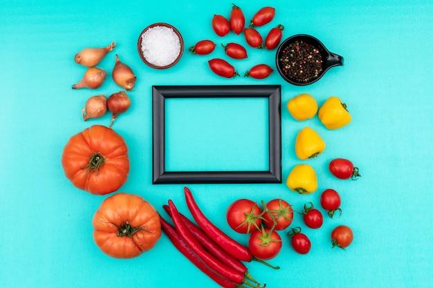 Struttura variopinta delle verdure circondata con pepe giallo dolce del sale marino della cipolla del pomodoro ciliegia del peperoncino rosso sulla superficie del blu