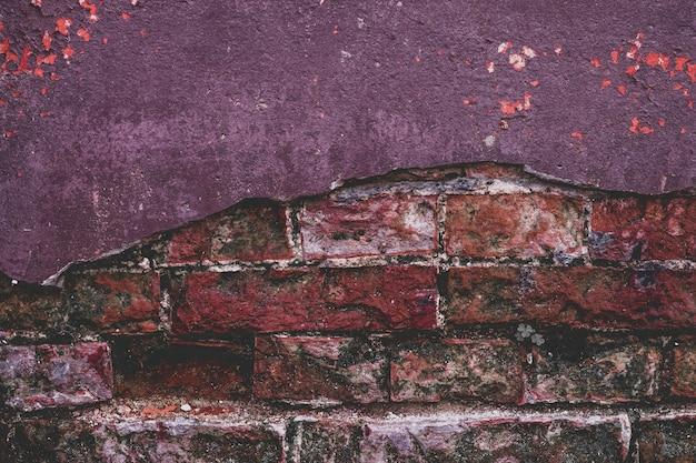 Struttura viola d'annata del muro di mattoni di lerciume e fondo bianco della facciata dello stucco bianco