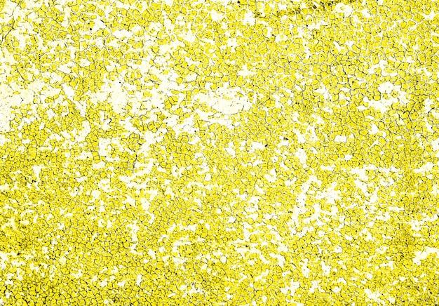 Strutturi il fondo di lerciume del muro di pietra concreto con la pittura della sbucciatura di colore giallo