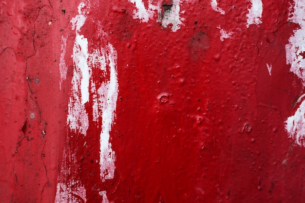 Strutturi il fondo di lerciume del muro di pietra concreto con la pittura della sbucciatura di colore rosso