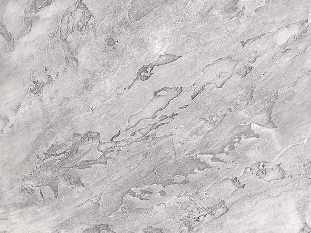 Strutturi il gesso grigio decorativo che imita la vecchia parete della sbucciatura.