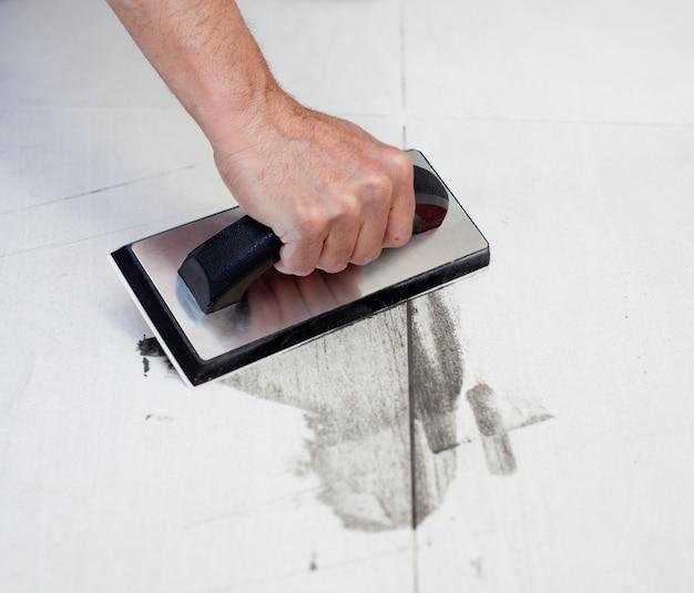Stuccatura di piastrelle con spatola di gomma man mano