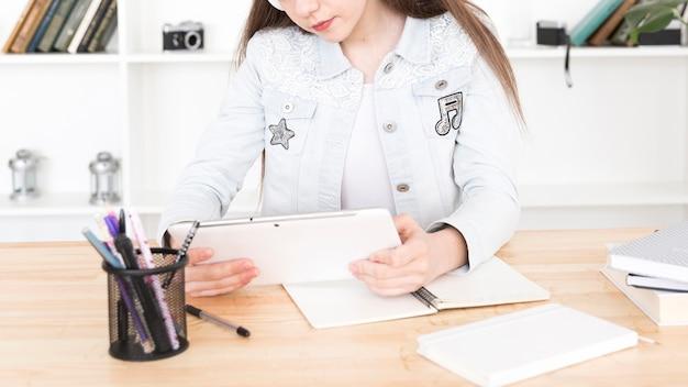 Studente adolescente che si siede al tavolo con tavoletta in mano