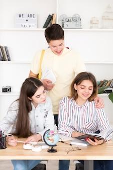Studente adolescente che sta vicino ai compagni di classe della ragazza che si siedono alla tavola
